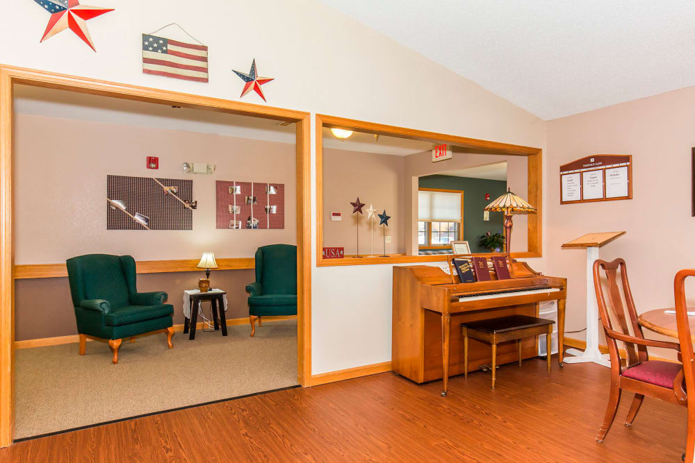 Cozy lounge area complete with armchairs and piano at Emerald Glen of Olney in Olney, Illinois