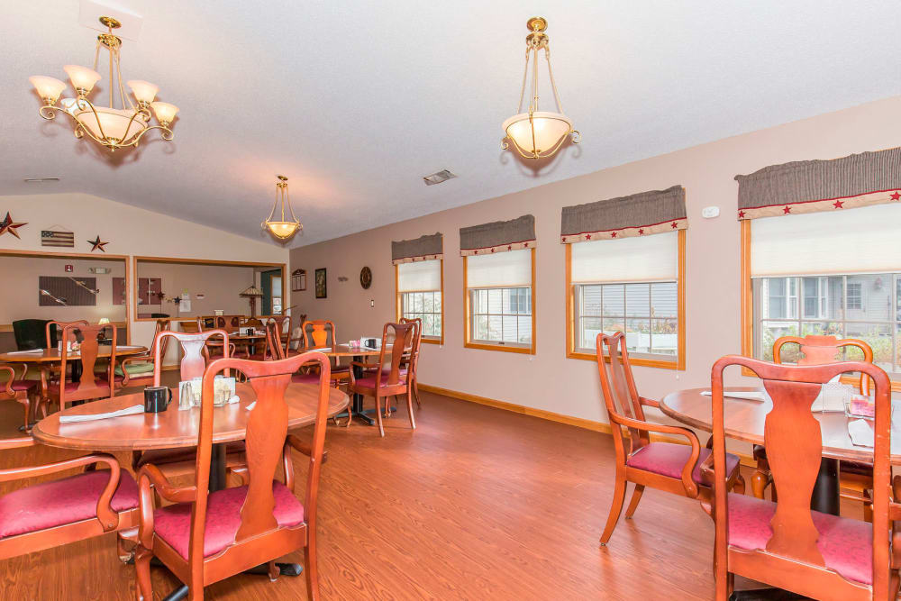 Elegant dining room with chandeliers and hardwood floor at Emerald Glen of Olney in Olney, Illinois