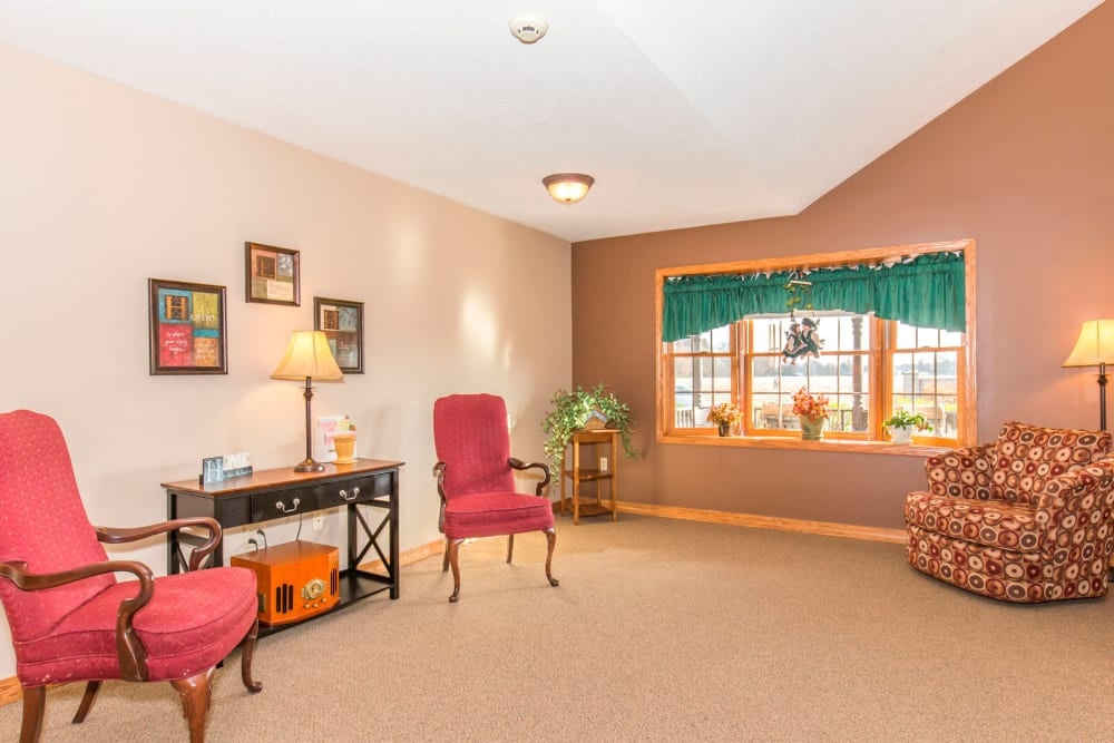 Airy and well lit sitting room complete with window and red chairs at Emerald Glen of Olney in Olney, Illinois