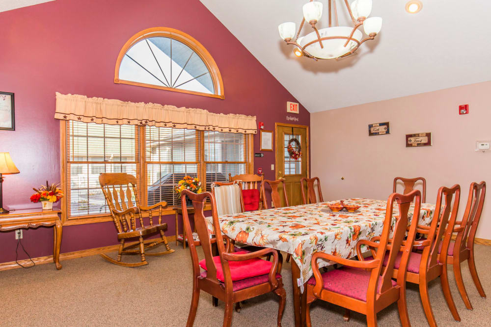 Elegant dining area with red wall, window, and chandelier at Emerald Glen of Olney in Olney, Illinois