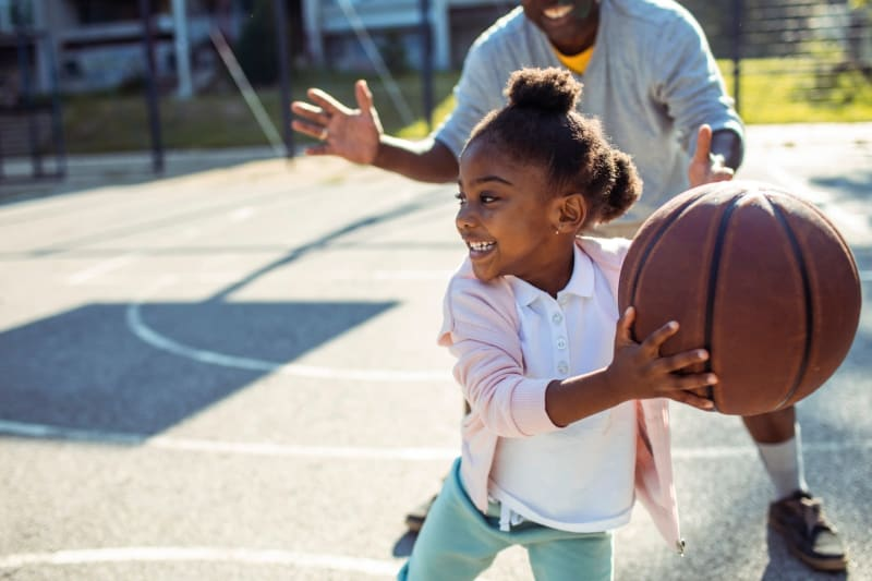 Father and daughter playing basketball at a park near Presley Oaks in Charlotte, North Carolina