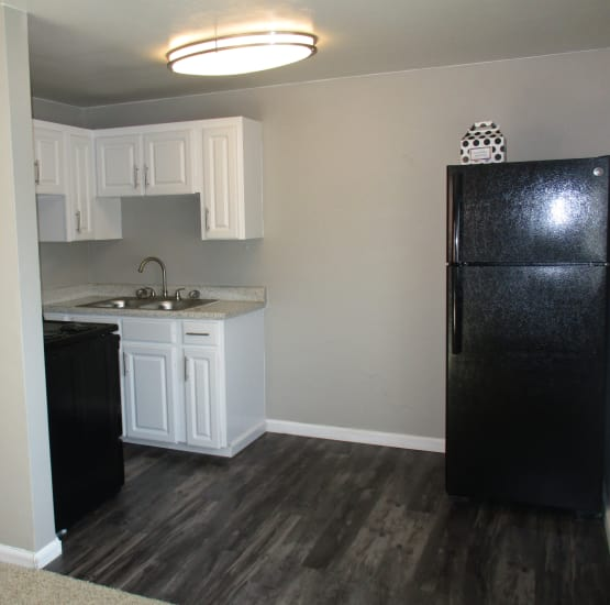 Modern kitchen with black appliances and faux hardwood floor at Lamar Station Apartments in Lakewood