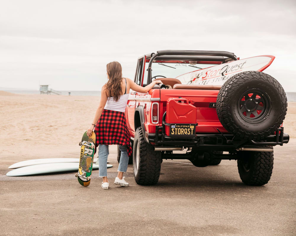 Woman with a skateboard leaning against a red jeep near StorQuest Self Storage in Santa Monica, California