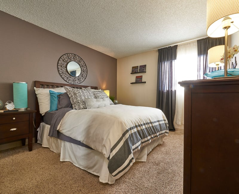Master bedroom with plush carpeting in a model home at Hampden Heights Apartments in Denver, Colorado