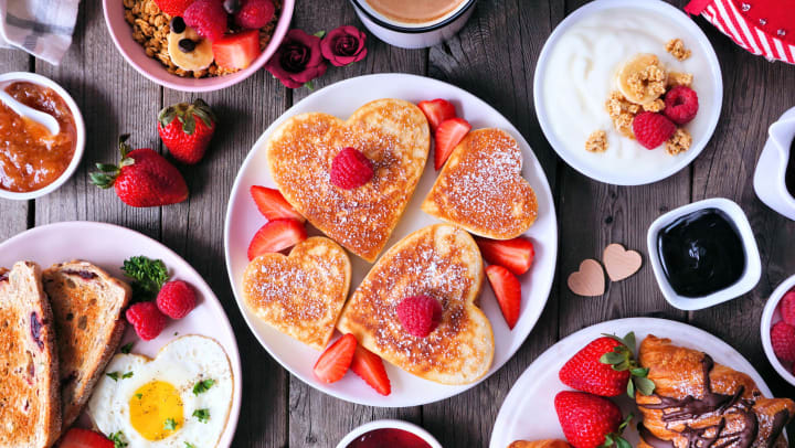 Various breakfast foods on a table with heart-shaped pancakes in the center with raspberries and strawberries on top.