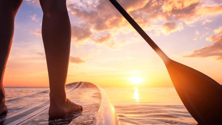 Close-up of stand up paddleboarding on a quiet sea at sunset.