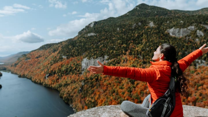 A person with arms stretched out looking out over a river next to mountains covered in fall colors