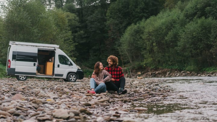 A forest and open van in the background. Rocky beach next to a stream. A man and a woman are sitting together on the rocky beach.