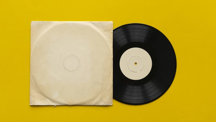Vinyl record partially in sleeve against a yellow background