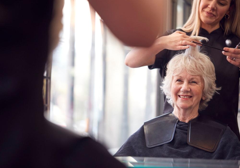 Resident getting a haircut at Kingston Bay Senior Living in Fresno, California.