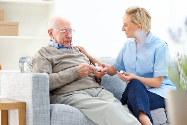 female caregiver sitting with senior man