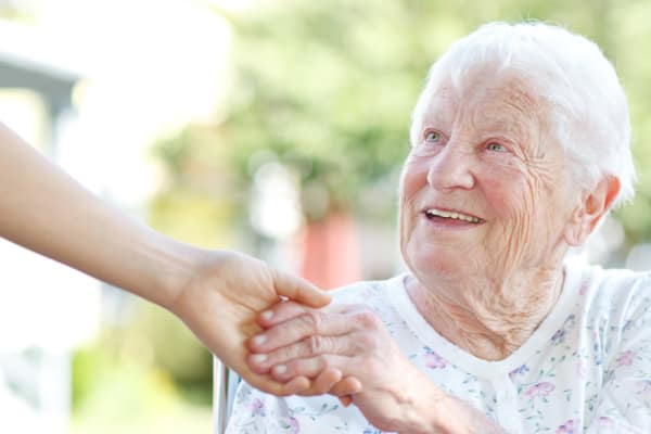 A resident of Ramsey Village Continuing Care holding her caregiver's hand in Des Moines, Iowa