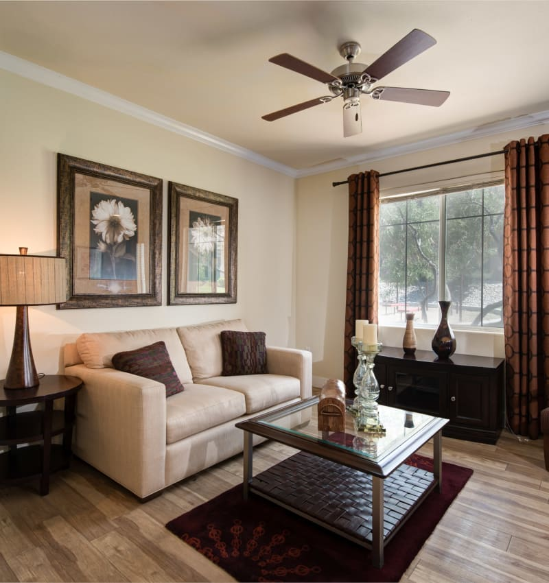 Well-furnished living area with hardwood floors and a ceiling fan in a model home at Broadstone Towne Center in Albuquerque, New Mexico