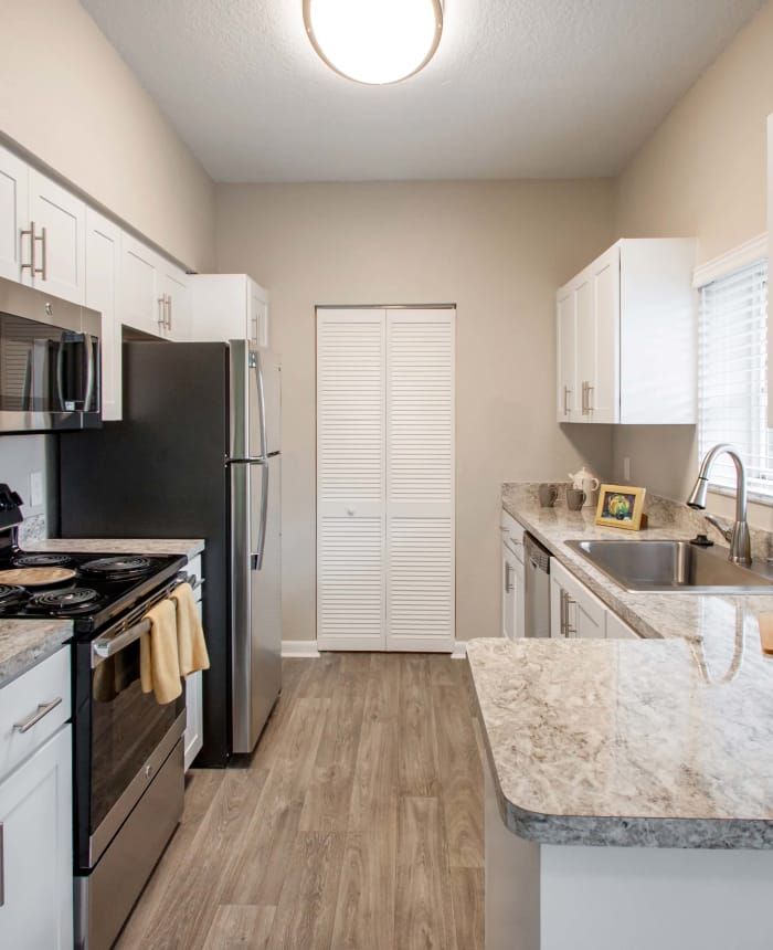 Kitchen with hardwood floors and stainless appliances in model home at IMT Pinebrook Pointe in Margate, FL