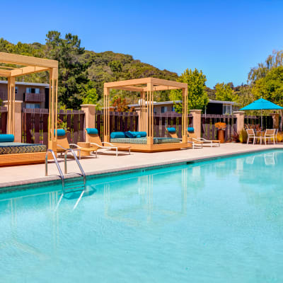 Cabanas and chaise lounge chairs around the pool at Sofi Belmont Hills in Belmont, California