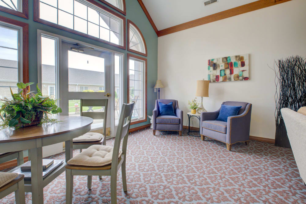Brightly lit room with foliage, artwork, and armchairs at Brookstone Estates of Vandalia in Vandalia, Illinois