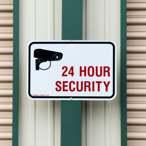 A sign for 24 hour security at Red Dot Storage in Adel, Iowa