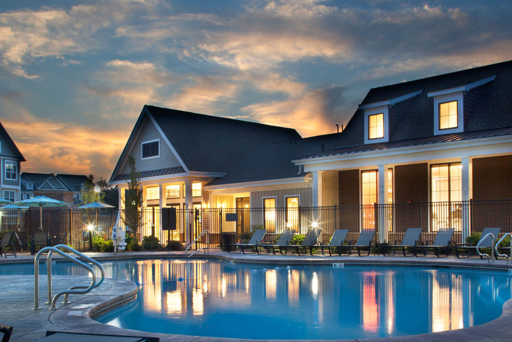 View of the swimming pool and resident clubhouse at dusk at Prynne Hills in Canton, Massachusetts