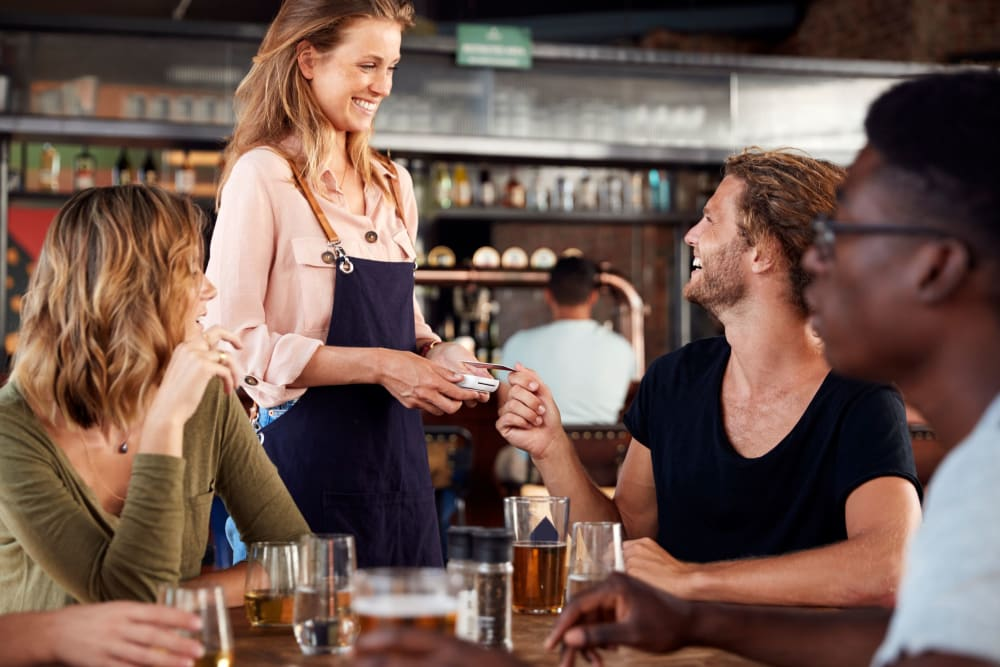 Friends chatting over drinks at a local bar in Sanford, Florida near Integra Crossings