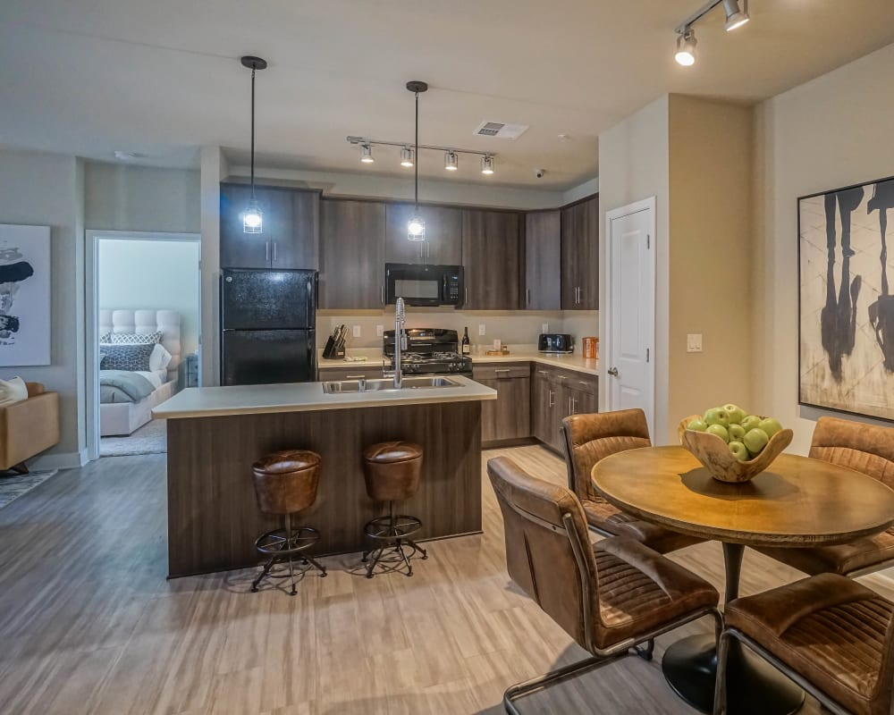 View of the gourmet kitchen from a model home's open-concept dining area at Olympus Northpoint in Albuquerque, New Mexico