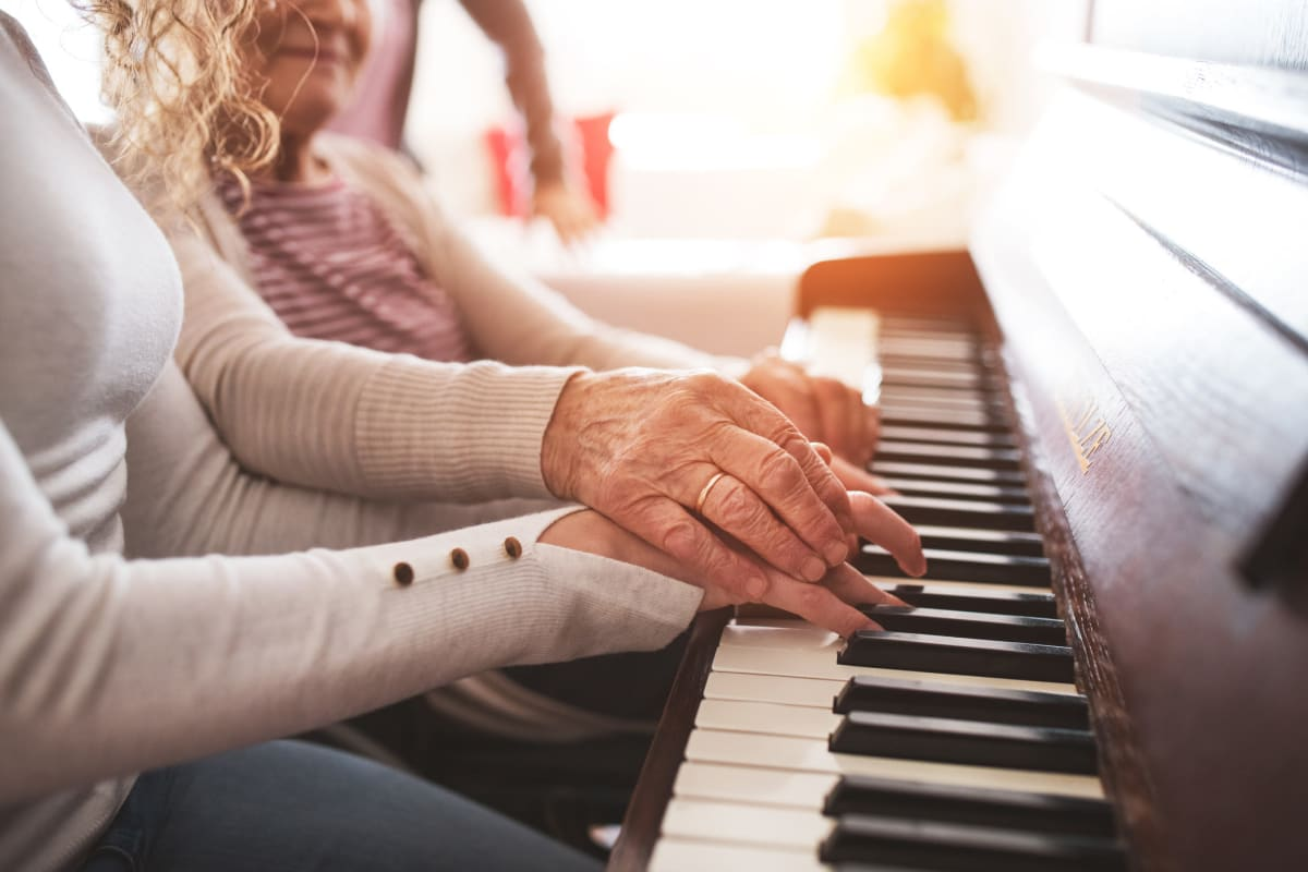 A resident playing the piano at Oxford Glen Memory Care at Sachse in Sachse, Texas