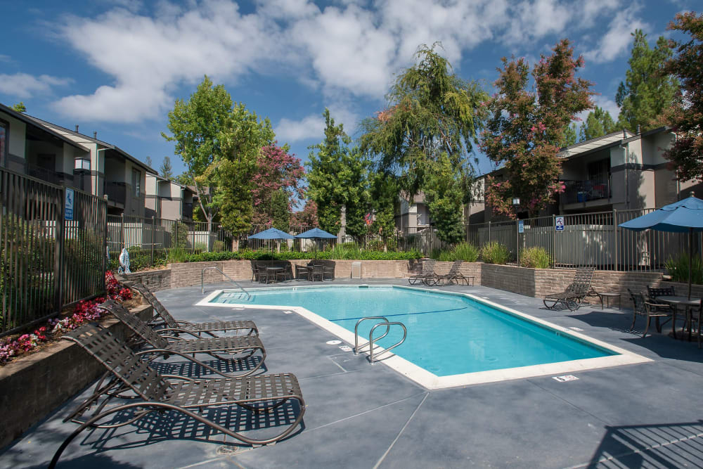 Spacious sundeck with table and chairs next to a swimming pool at Valley Ridge Apartment Homes in Martinez, California