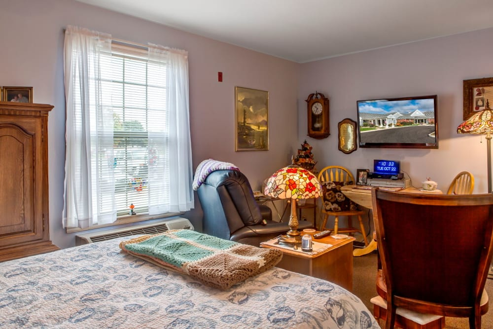 Cheerful apartment in upscale senior living facility complete with bed, seating, and television set at Carriage Court of Grove City in Grove City, Ohio