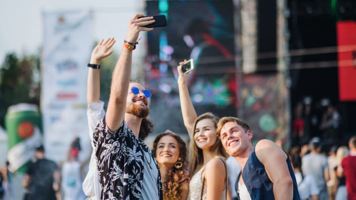 A group of five friends at an outdoor concert. The concert is in the background as the tallest male holds up his phone to take a picture, the other four wave.