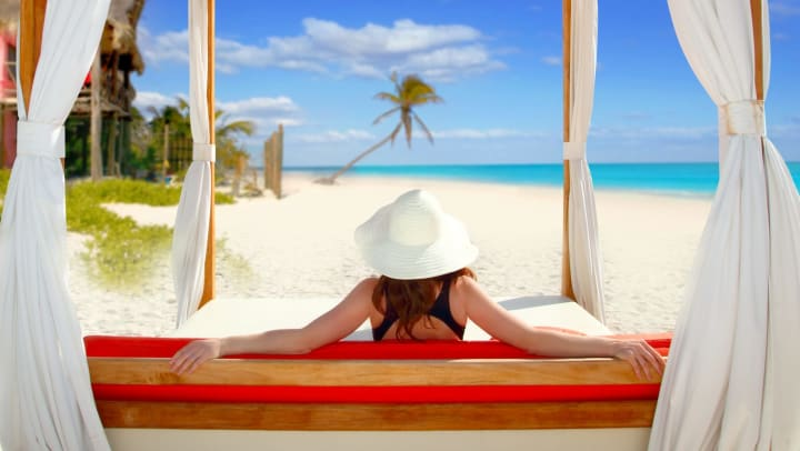 Woman reclining on a padded bench in a cabana on the beach, with her back to the camera.