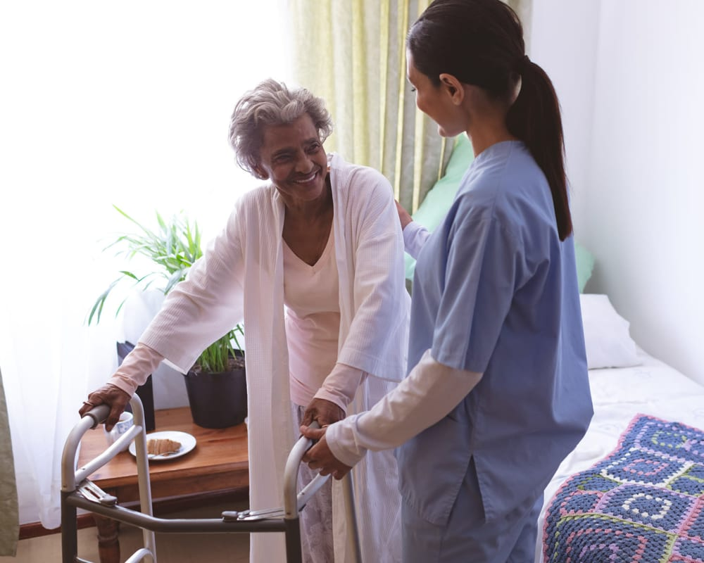 Resident with a walker talking to a nurse at Keepsake Village at Greenpoint in Liverpool, New York