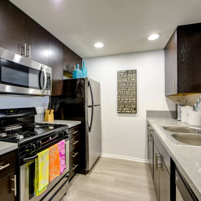 Modern kitchen with granite countertops and stainless-steel appliances in a model home at Sofi at 3rd in Long Beach, California