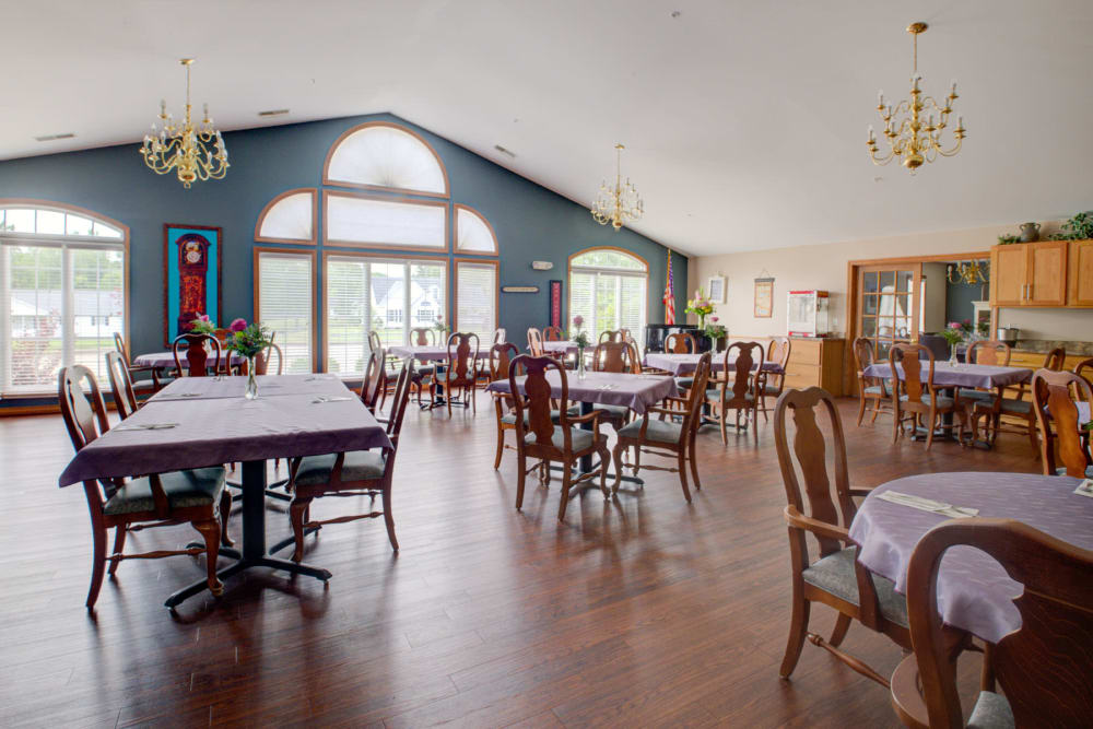 Sunny dinning room with wood accents and chandeliers at Brookstone Estates of Vandalia in Vandalia, Illinois