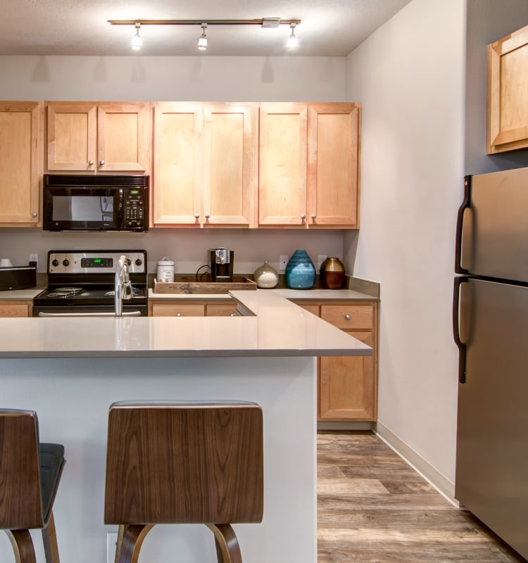 Modern kitchen with sleek, stainless-steel appliances and quartz countertops in a model home at Sofi at Forest Heights in Portland, Oregon