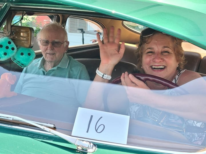 A West Covina (CA) resident and his family member take a picture in a classic car.