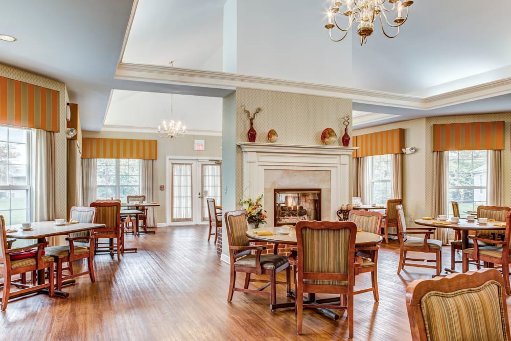 Ornate dining room complete with wood accents and chandeliers at Carriage Court of Grove City in Grove City, Ohio