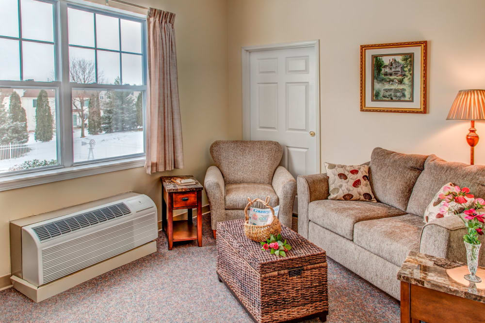Comfy apartment in upscale senior living facility complete with armchairs and rustic snowy view at Grand Victorian of Rockford in Rockford, Illinois