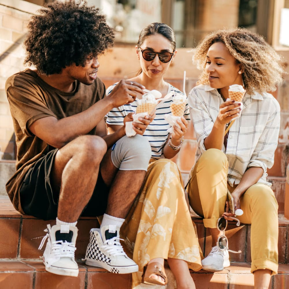 Resident friends hanging out on a downtown stoep enjoying ice cream near Oaks Estates of Coppell in Coppell, Texas