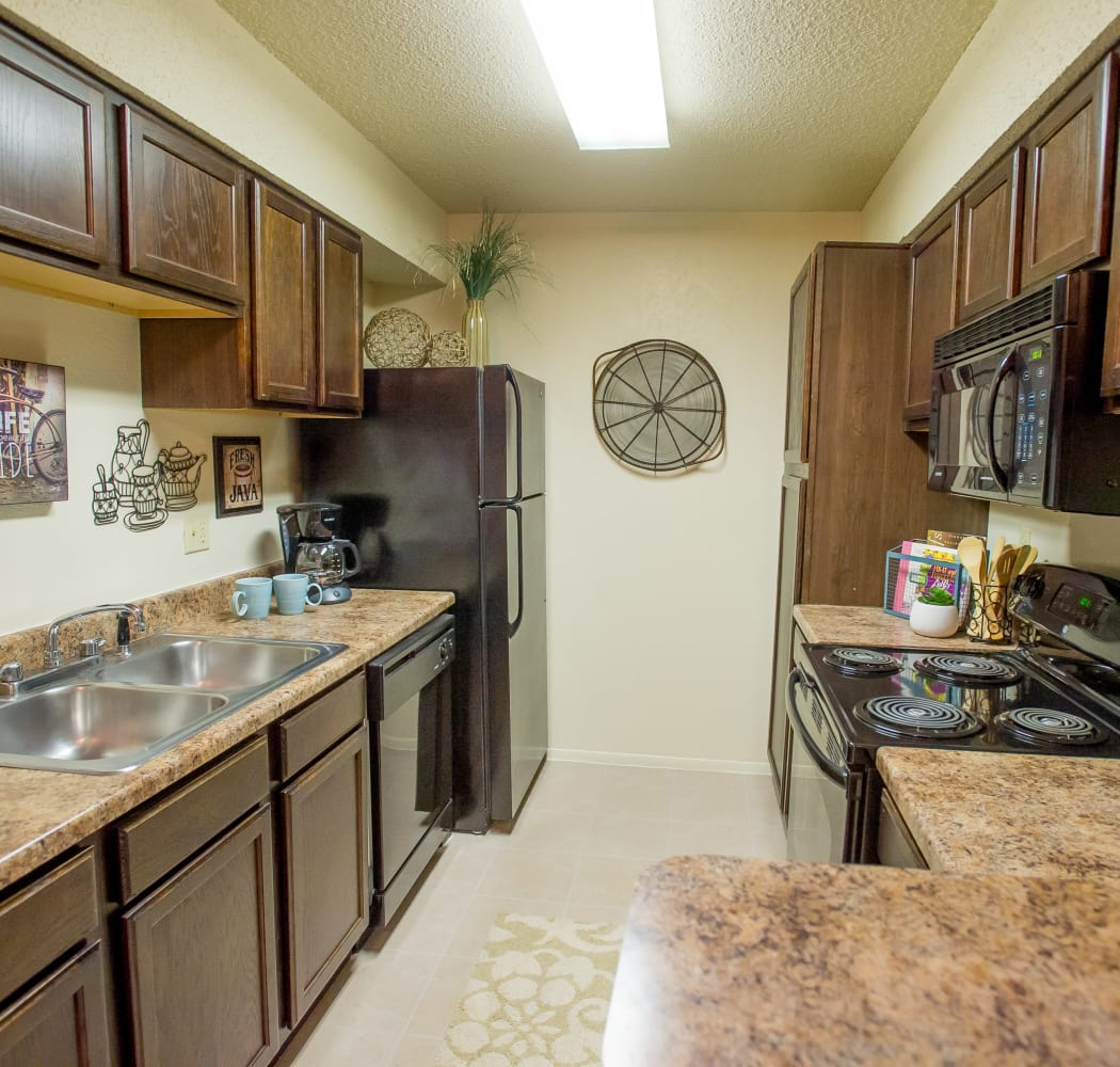 Modern kitchen with all the necessities in model home at Sugarberry Apartments in Tulsa, Oklahoma