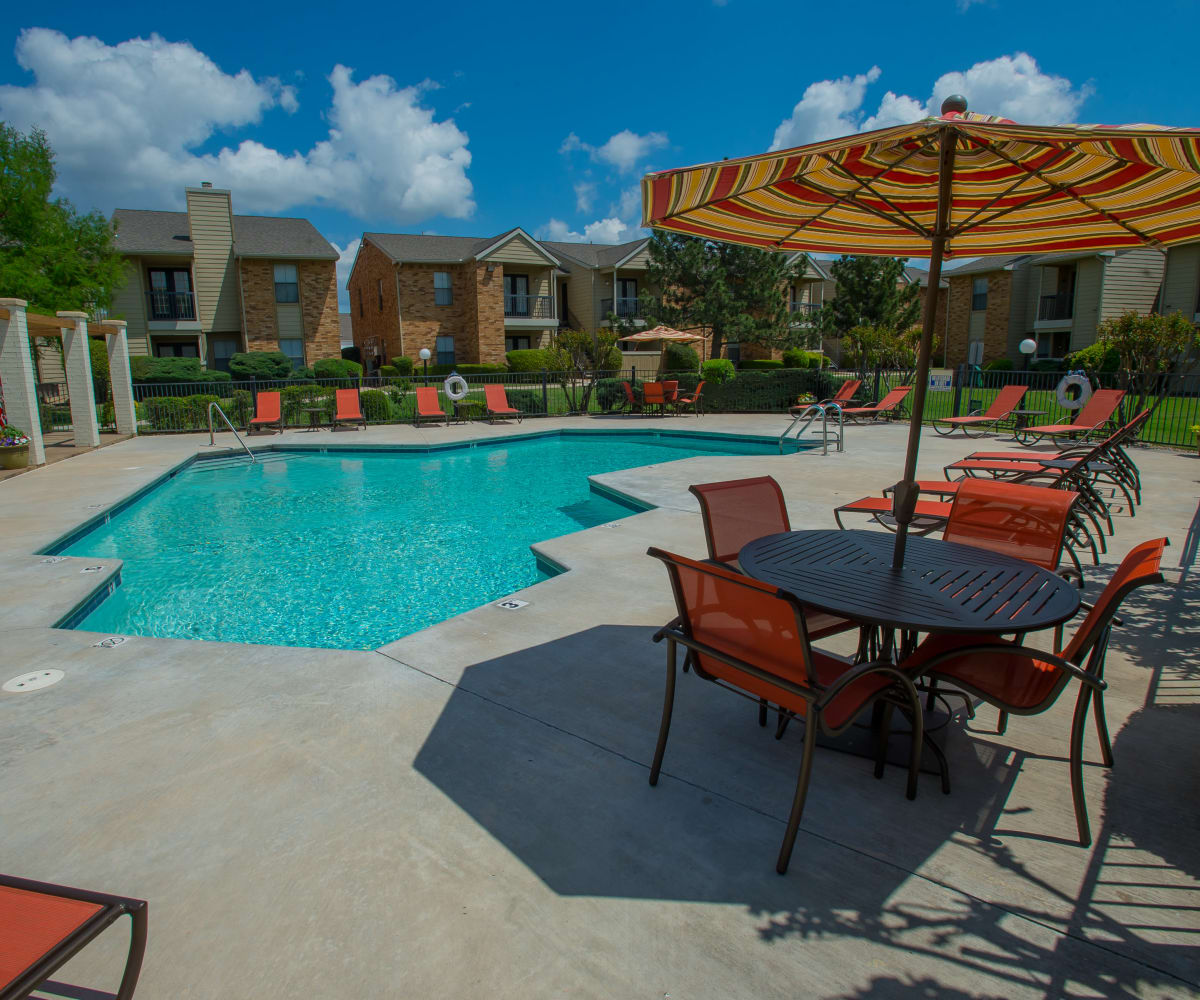 Covered outdoor tables by the pool at Cimarron Trails Apartments in Norman, Oklahoma