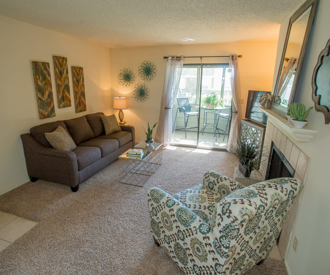 Living room with fireplace looking out onto private balcony of model home at Sugarberry Apartments in Tulsa, Oklahoma