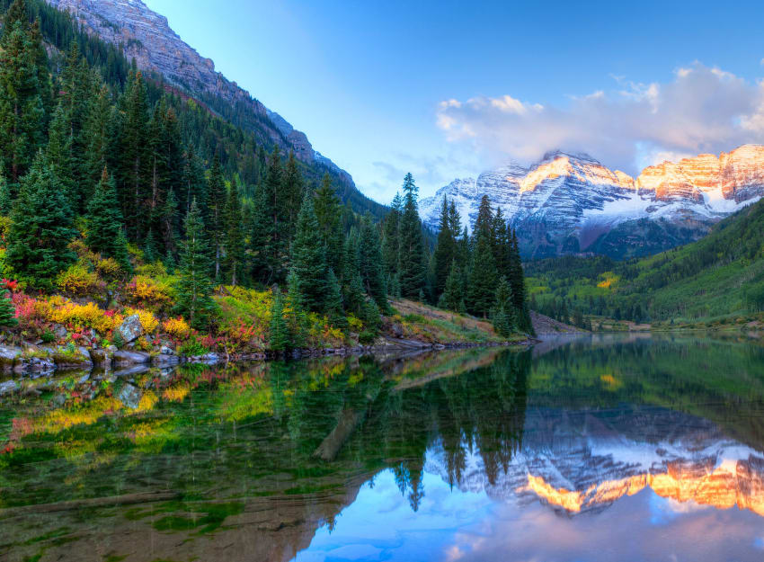 Beautiful mountains and trees reflecting on mountain lake in Colorado.