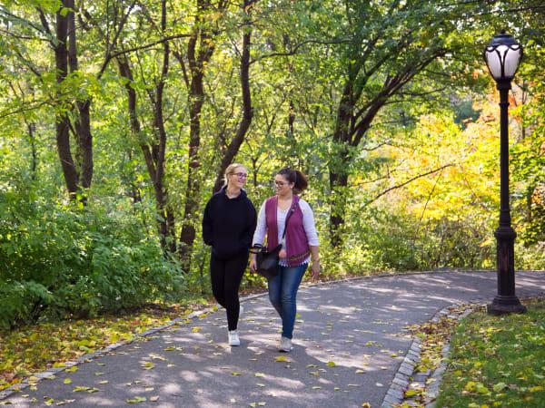 Friends walking through a park at Olde Hampton Village Apartments in Hampton, New Hampshire