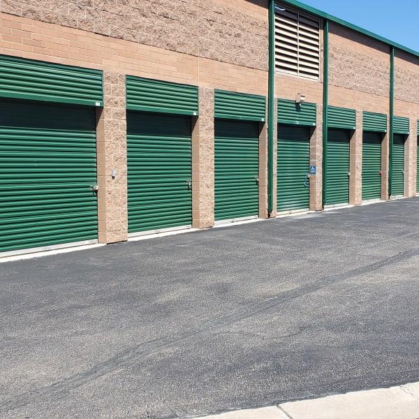 Outdoor storage units with green doors at StorQuest Self Storage in Aurora, Colorado