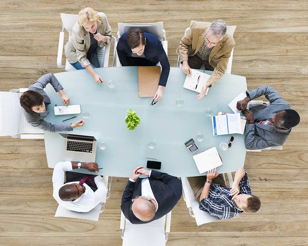 Overhead view of employees at a meeting around a table at American Capital Group in Bellevue, Washington