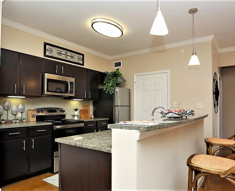 Spacious kitchen with a breakfast bar overlooking the living room at Trails at Lake Houston in Houston, Texas