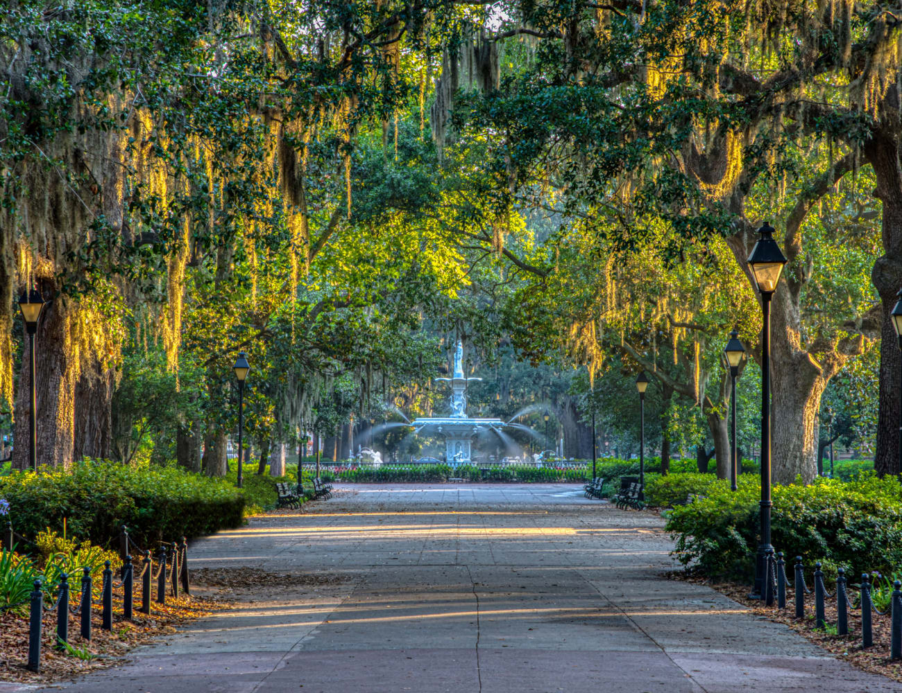 Beautiful canopy of mature trees shading the pathway to a park's fountain near The Bentley at Marietta in Marietta, Georgia