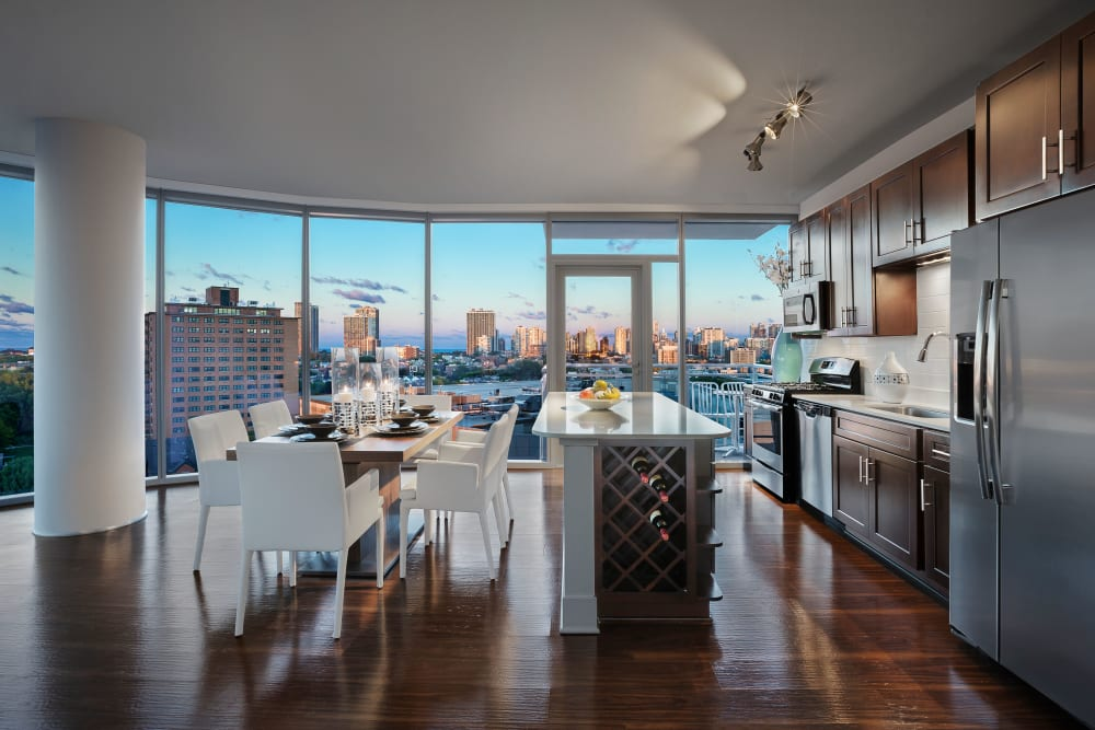 Kitchen with an overview of the living room at The Residences at NEWCITY in Chicago, Illinois