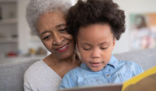 Grandma and her grandson reading a book together at Inspired Living Alpharetta in Alpharetta, Georgia