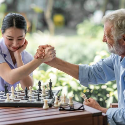 Resident and caregiver playing chess at The Sanctuary at West St. Paul in West St. Paul, Minnesota