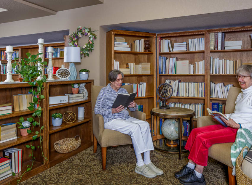 Resident reading books in the library at Ramsey Village Continuing Care in Des Moines, Iowa